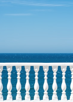 Classic roman white concrete railing outside the building on the terrace or promenade overlooking the sea with blue sky and clouds