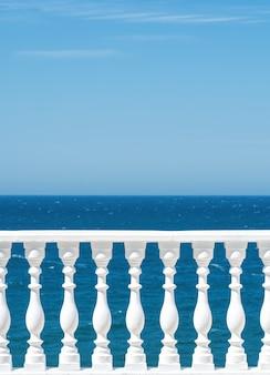 푸른 하늘과 구름과 함께 바다가 내려다 보이는 테라스 또는 산책로에 건물 외부의 고전적인 로마 흰색 콘크리트 난간