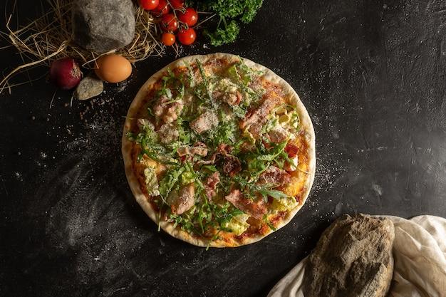 ベーコン、ルッコラ、すりおろしたパルメザンチーズを使ったクラシックな丸い薄いクラストピザ。