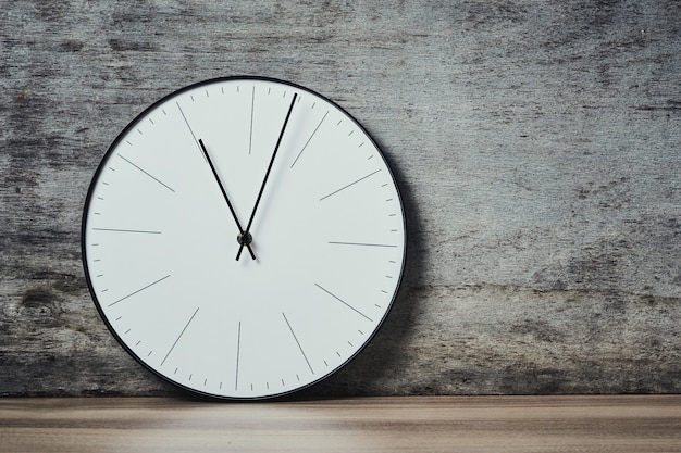 Classic round wall clock on a wooden background with copy space