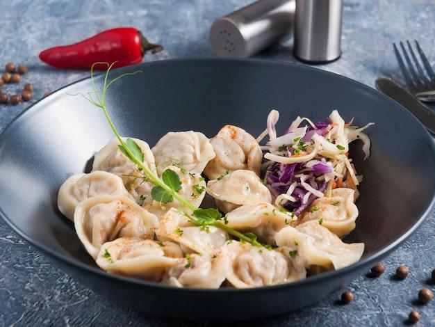 暗いプレートの野菜サラダからの肉とpodgarnirovokyと古典的なロシアの餃子