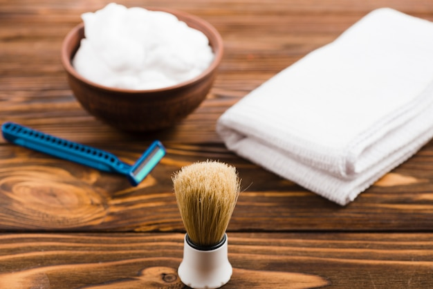 Classic shaving brush in front of foam bowl; folded white napkin and razor on wooden desk