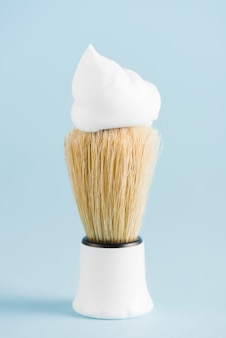 The classic shaving brush with foam against blue backdrop