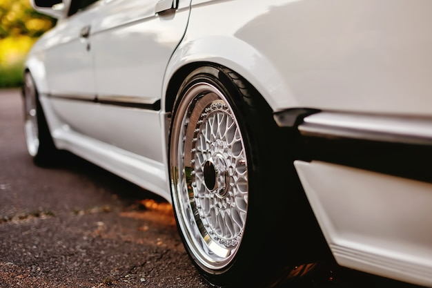 흰색 차에 클래식 반짝 복고풍 바퀴입니다.