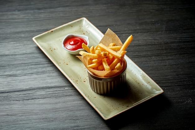 Классический гарнир - картофель фри с красивой сервировкой на тарелке с красным соусом