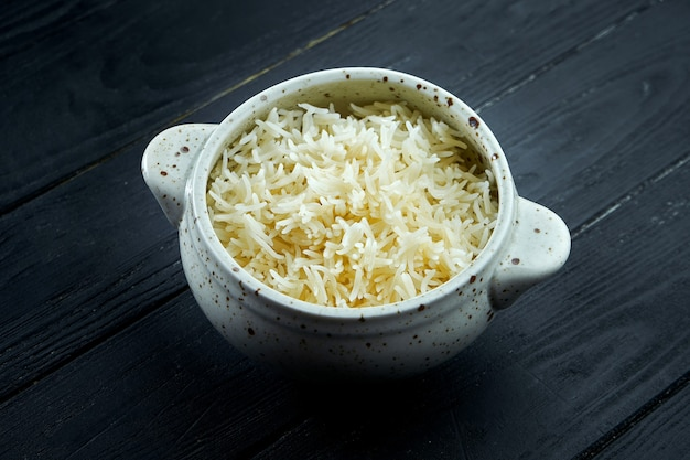 The classic side dish is saffron rice in a white bowl. diet and vegetarian food. dark wooden background