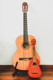 Classic six-string wooden guitar and hawaiian four-string guitar ukulele stand against the wall. comparison of musical string instruments.