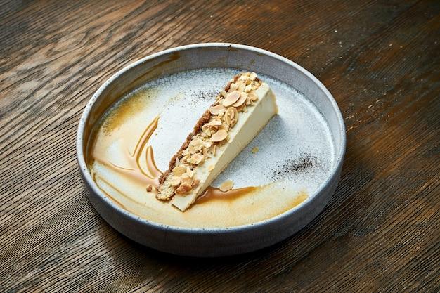 アーモンドとキャラメルソースを添えたチーズケーキのクラシックなスライス。木製のテーブルの上の白いプレートでお召し上がりいただけます。レストランの食べ物。食欲をそそるデザート