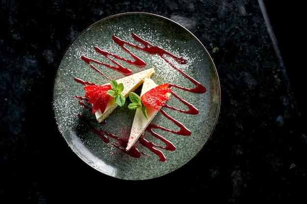 大理石のテーブルの上の黒いプレートで提供される、イチゴ、キャラメル、ミントを添えたチーズケーキの古典的なスライス。レストランの食べ物。食欲をそそるデザート