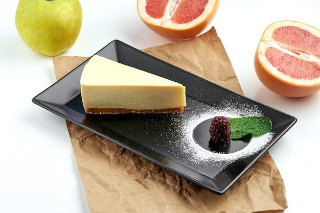 Классический кусок чизкейка new york подается в черной тарелке на белой поверхности. еда в ресторане