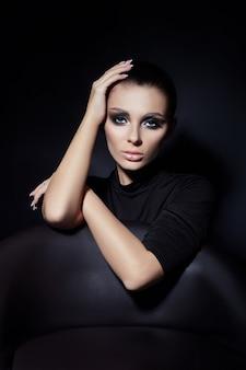 女性の顔にクラシックなスモーキーメイク、美しい大きな目。ファッション パーフェクトなメイク、滑らかな黒眉、ブルネットの髪