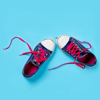 Classic sneakers over light blue background, above view. image with space for text or other design