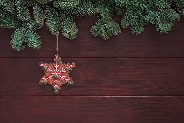 Classic snowflake shaped holiday ornament and spruce tree border on brown wooden background