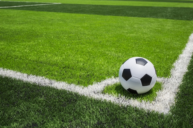 Classic soccer ball on artificial bright and dark green grass