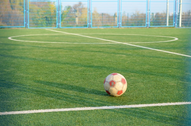 Classic soccer ball on football green grass field outdoor. active sports and physical training