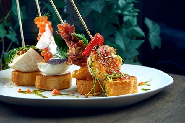 古典的なスペインの前菜-エビ、カマンベール、サーモン、ハモンの白い皿にピンチョスまたはタパス。セレクティブフォーカス
