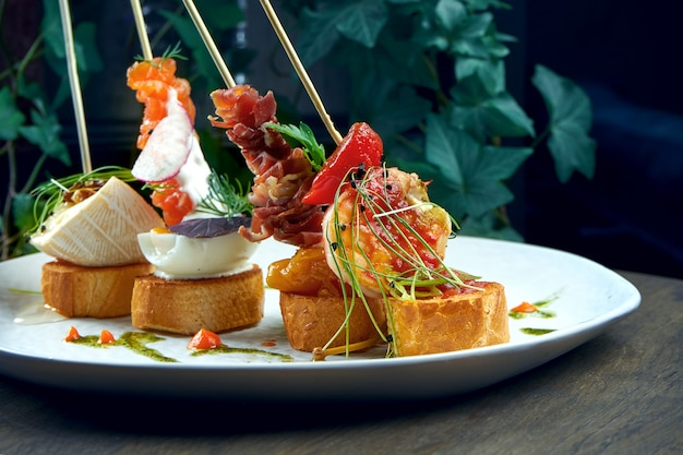 Classic spanish antipasto - pintxos or tapas with shrimp, camembert, salmon and jamon in a white plate. selective focus