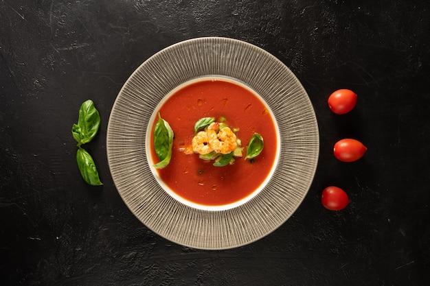 黒い石のキッチンテーブルにエビ、バジルの葉、チェリートマトを添えたクラシックなスペインのトマトスープガスパチョ