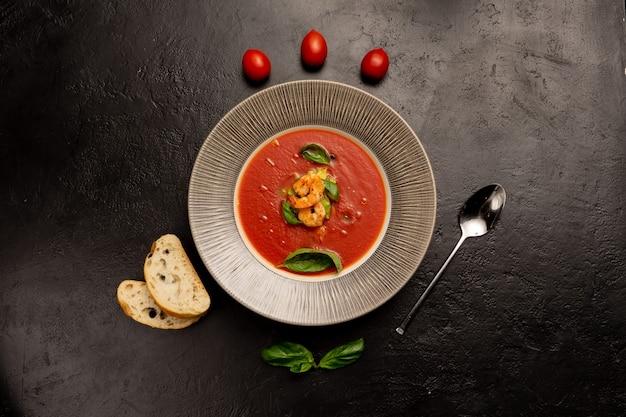 黒い石のキッチンテーブルにエビ、バジルの葉、チェリートマト、チャバタのチャンクが入ったクラシックなスペインのトマトスープ