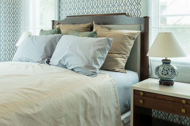 Classic style bedroom with blue pillows and chinese lamp style on bedside table