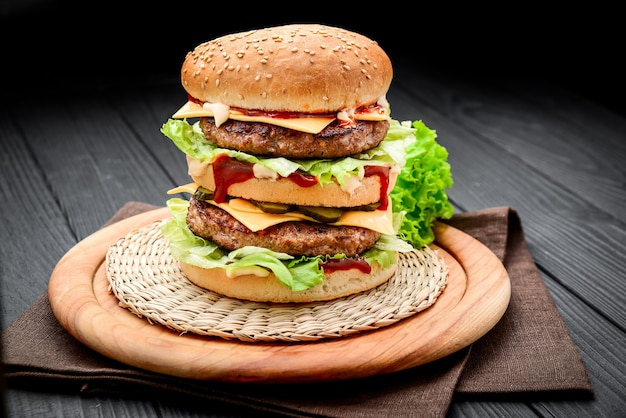 A classic style double cheeseburger with two beef patties, sauce, lettuce, cheese, pickles, and onions on a sesame seed bun