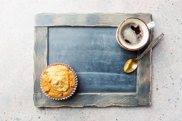 灰色の石のテーブルにチップマフィンとコーヒーカップで撮影したクラシックなスタイルのエスプレッソ上面図