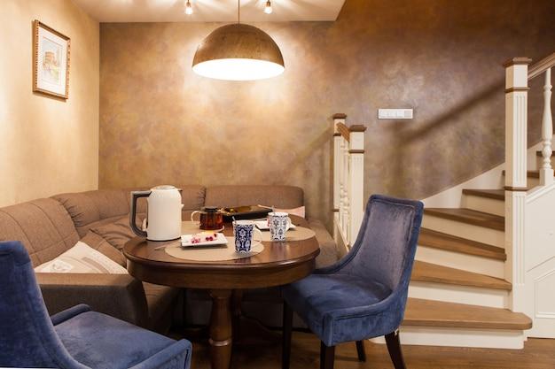 Классический стиль интерьера гостевой комнаты в двухуровневой квартире. обеденный стол и стулья, белая деревянная лестница на второй этаж со встроенными шкафчиками.