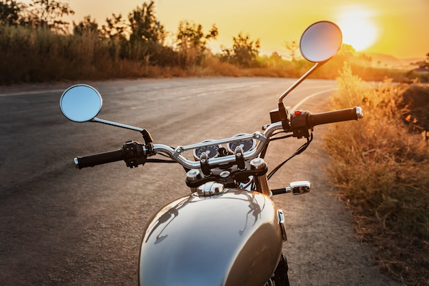 Classic style motorcycle on road with sunset
