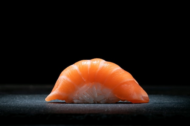 Classic sushi nigiri with salmon on a dark stone