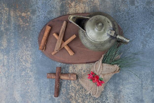 Teiera classica e bastoncini di cannella sul piatto di legno. foto di alta qualità