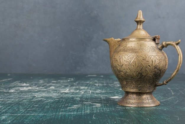 Classic teapot isolated on marble table.