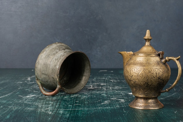 Teiera e vaso classici sulla tavola di marmo.