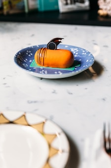 Classic thai tea mousses cake decorated with chocolate in blue plate on marble top table.
