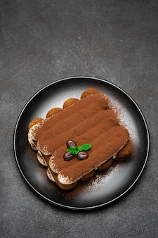 Classic tiramisu dessert on ceramic plate on dark concrete background