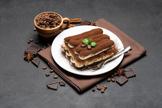 Classic tiramisu dessert on a ceramic plate on dark concrete background