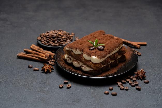Классический десерт тирамису на керамической пластине на бетонном фоне