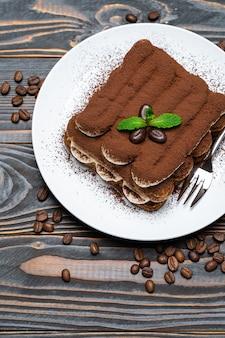 Классический десерт тирамису на керамической тарелке на деревянном фоне