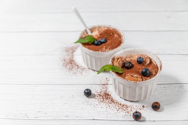 Classic tiramisu dessert with blueberries, mint in white jar on grey