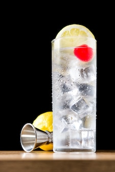 Classic tom collins cocktail on wooden table and black