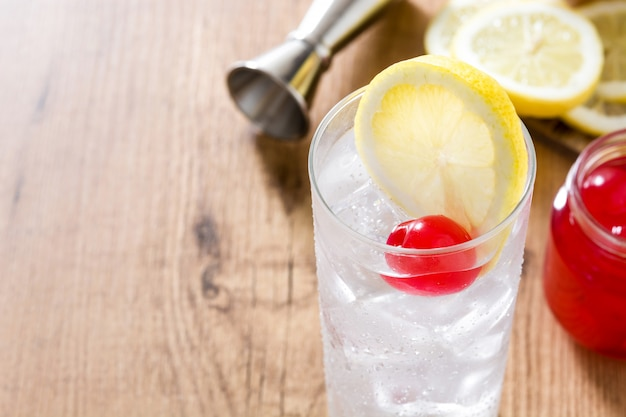Classic tom collins cocktail on wooden table copyspace
