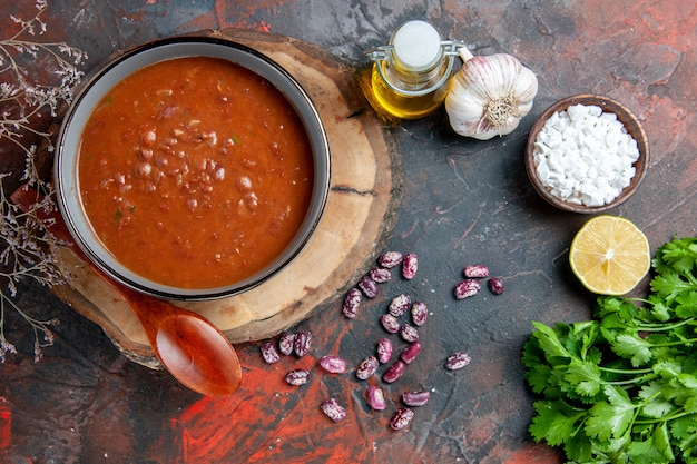 Classic tomato soup in a blue bowl spoon on wooden tray oil bottle garlic salt and lemon a bunch of green on mixed color table