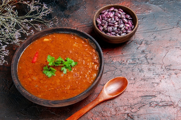 Classic tomato soup in a brown bowl beans and spoon on mixed color table