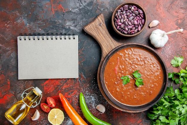 혼합 색상 테이블에 커팅 보드에 클래식 토마토 수프 타락한 기름 병 콩 및 노트북