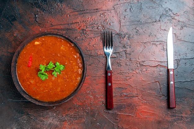 混合色のテーブルに茶色のボウルとスプーンで古典的なトマトスープ