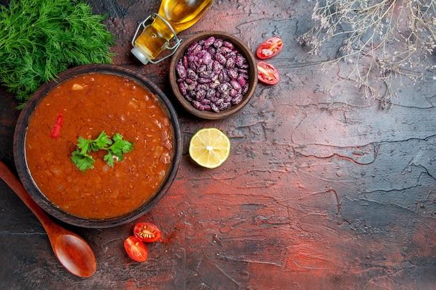 茶色のボウル豆の古典的なトマトスープと混合色のテーブルに油のボトルをスプーンでスプーン