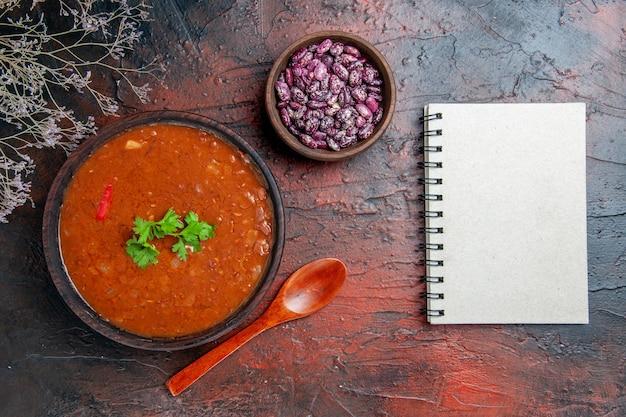 混合色のテーブルのノートの横にある茶色のボウル豆とスプーンの古典的なトマトスープ