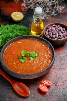 混合色のテーブルに茶色のボウル豆とスプーンオイルボトルの古典的なトマトスープ