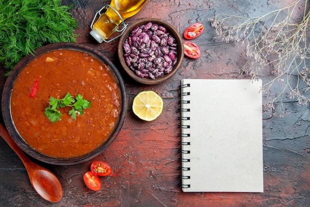 茶色のボウル豆のスプーンとノートの古典的なトマトスープ混合色のテーブルに油のボトル