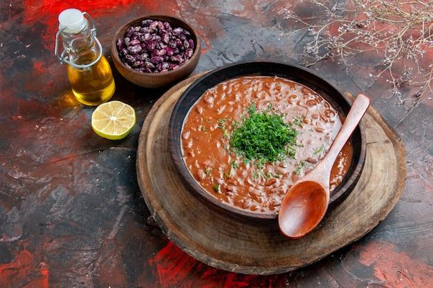 Классический томатный суп в коричневой чаше с маслом бутылки и ложкой на столе смешанного цвета