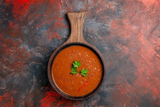 混合色のテーブルの茶色のまな板の上の古典的なトマトスープ